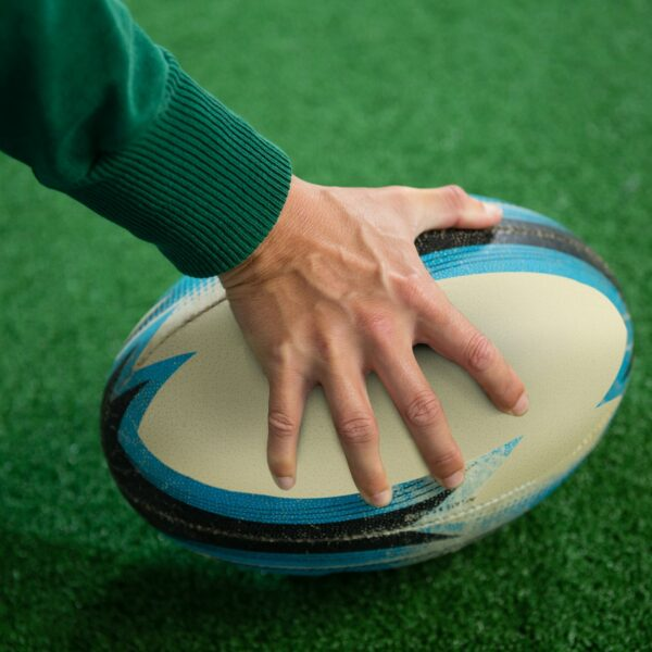 Cropped hand holding rugby ball